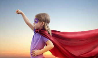 Child in a cape and mask playing superhero